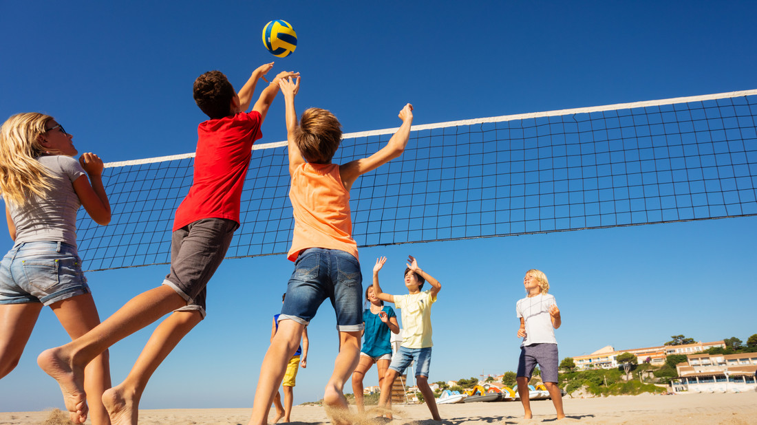 Kinder spielen Volleyball am Strand.